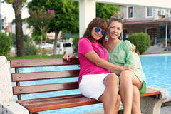 Mother and daughter sitting on a bench in the park Stock Images