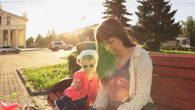 Mother and daughter are sitting on a bench on a square near the road at sunset. stock video