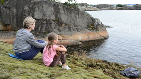Mother and daughter sitting on the big stones on the sea shore. Looking at water stock video footage