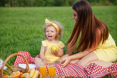 Mother and daughter sitting on blanket in park Stock Photo
