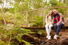 Mother and daughter sitting on a bridge in a forest Royalty Free Stock Images