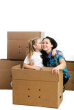 Mother and daughter. Sitting between cardboard boxes Royalty Free Stock Photo