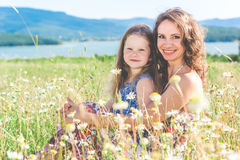 Mother and daughter are sitting in chamomile field Stock Photos