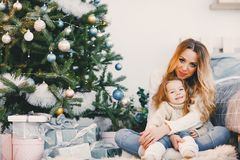 Mother and daughter sitting by the christmas tree. Mother hugging daughter and sitting by the christmas tree Royalty Free Stock Image