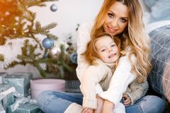 Mother and daughter sitting by the christmas tree. Mother hugging daughter and sitting by the christmas tree Stock Photography