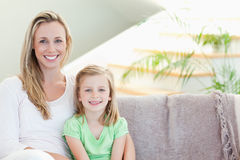 Mother and daughter sitting on couch together Royalty Free Stock Photos