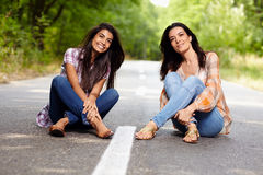 Mother and daughter sitting cross legged on the road. In a forest Royalty Free Stock Photo
