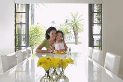 Mother And Daughter Sitting At Dining Table Royalty Free Stock Photography