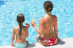 Mother and daughter sitting on edge of pool with drink Royalty Free Stock Image