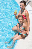 Mother and daughter sitting on edge of pool with drink Stock Photos