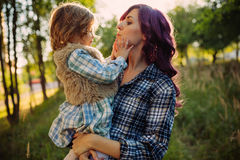 Mother and daughter sitting on the field in sunset Royalty Free Stock Photography