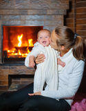 Mother and daughter sitting by a fireplace in their family home Stock Images