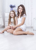 Mother and daughter sitting on the floor and hugging each other Royalty Free Stock Photo