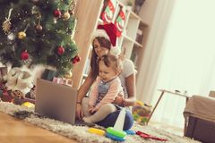 Watching cartoons. Mother and daughter sitting on the floor next to a Christmas tree, watching cartoons on a laptop computer and having fun. Focus on the baby royalty free stock images