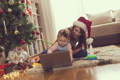 Christmas morning cartoons. Mother and daughter sitting on the floor next to a Christmas tree, watching cartoons on a laptop computer and having fun. Focus on royalty free stock photos