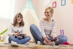 Mother and daughter playing video games. Mother and daughter sitting on the floor in a playroom, playing video games and having fun. Focus on the mother Royalty Free Stock Images