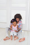 Mother and daughter sitting on the floor reading storybook Stock Photo