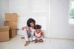 Mother and daughter sitting on the floor reading storybook i Stock Photos
