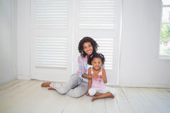 Mother and daughter sitting on the floor showing new house key Stock Images