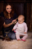 Mother and daughter sitting on the floor together Stock Photography