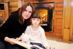 Mother and daughter sitting in front of fireplace Royalty Free Stock Image