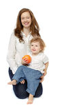 Mother and daughter sitting with fruit. Daughter sits on his lap mother holding a grapefruit on a white background stock image