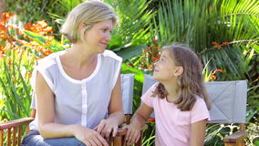 Mother And Daughter Sitting In Garden Chairs And Talking stock footage