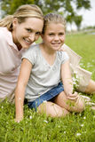 mother and daughter sitting on grass with flowers Stock Images