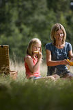 A mother and daughter sitting on the grass, having a picnic Stock Photos