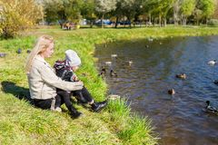 The mother with daughter sitting on grass and looking at lake with ducks royalty free stock photography