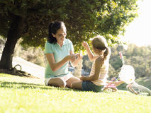 Mother and daughter (6-8) sitting on grass in park, making daisy chain, surface level (tilt) Royalty Free Stock Image