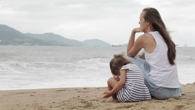 Mother with a daughter sitting with his back to the camera on the sandy beach. stock video