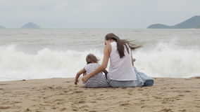 Mother with a daughter sitting with his back to the camera on the sandy beach. stock footage