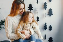 Mother and daughter sitting by holiday decorations royalty free stock image