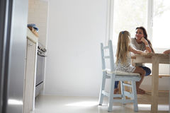 Mother And Daughter Sitting At Kitchen Table And Talking Stock Image