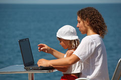 Mother and daughter sitting at laptop Stock Photo