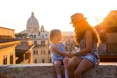 Mother and daughter sitting on ledge at sunset in Rome Stock Images
