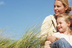 Mother And Daughter Sitting In Long Grass Stock Images