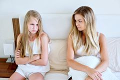 Mother and daughter sitting on a mattress looking sad stock photos