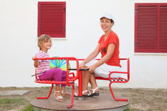 Mother and daughter sitting on merry-go-round Royalty Free Stock Photos