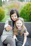 Mother and daughter sitting in nature and talking selfie Royalty Free Stock Photo