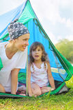 Mother and daughter sitting near tent Stock Photo