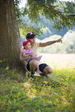 Mother and daughter sitting near a tree. Outside Royalty Free Stock Photo
