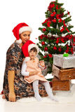 Mother and daughter sitting near Xmas tree Stock Photos