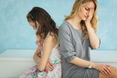 Mother and daughter are sitting next to each other back to back, do not talk. Conflict stock images