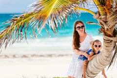Mother and daughter sitting on palm. At perfect Caribbean beach royalty free stock photography
