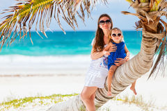 Mother and daughter sitting on palm Stock Images
