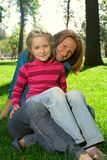 Mother and daughter are sitting at the park Stock Image