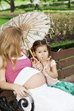 Mother and daughter sitting on a park bench Stock Photography