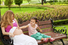 Mother and daughter sitting on a park bench Royalty Free Stock Photography